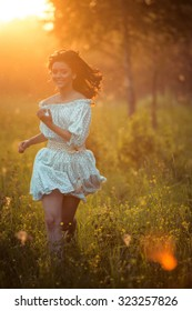beautiful girl on a walk in the park at sunset in a dress