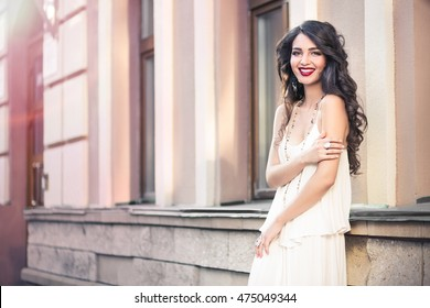 Beautiful girl on white dress walking on a warm sunny day in the city. Young brunette long-haired beautiful woman, lifestyle concept