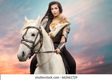 Beautiful girl on a white horse and with long hair in armor. A warrior, a knight in chain mail and with a sword on a white horse against a beautiful sky. Woman is a Viking. Fantasy