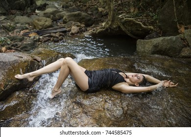 Beautiful girl on a wonderful nature resting on vacation near a waterfall in a dress