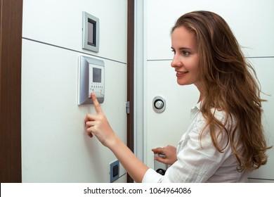 The beautiful girl the opening door of the apartment using video door phone of intercom system.