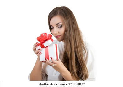 beautiful girl opening white box with a red bow. in the box is a gift. isolated