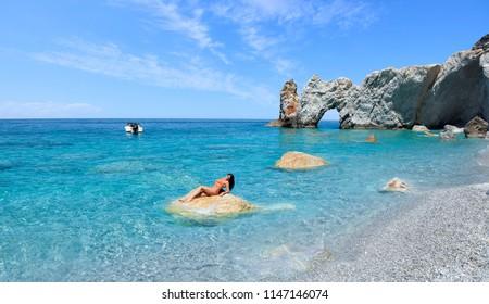 Beautiful girl in an orange bikini is relaxing on a rock on a very beautiful beach called Lalaria in Skiathos.