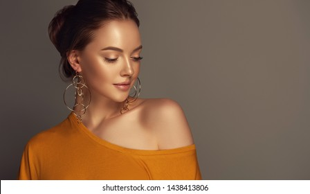 Beautiful girl in orange blouse on one shoulder . Fashionable and stylish women's clothing . Fashion look  , beauty and style. Young woman in trendy jewelry earrings rings.