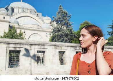 Beautiful girl with orange colored dress posing in front of the Suleymaniye Mosque