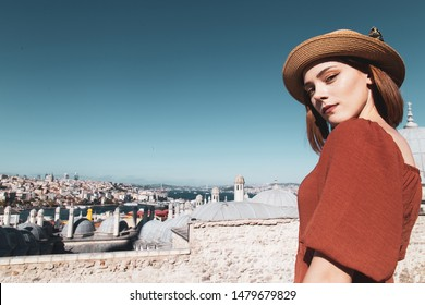 Beautiful girl with orange colored dress posing with Istanbul Scene