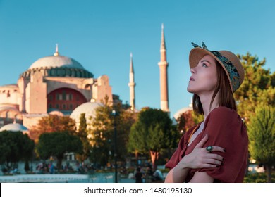 Beautiful girl with orange colored dress posing with Hagia Sophia during sunset from Istanbul