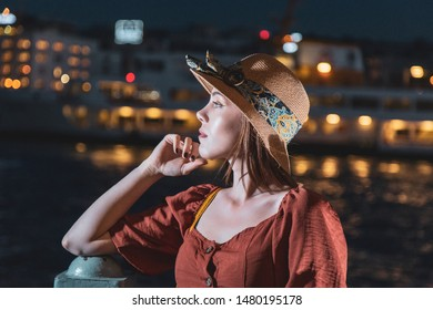 Beautiful girl with orange colored dress posing with citty ferry and Istanbul scene during twilight