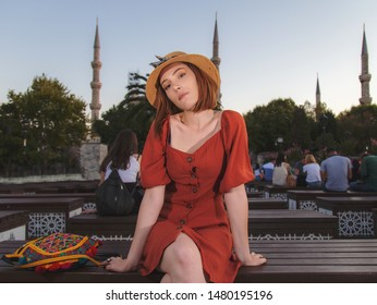 Beautiful girl with orange colored dress posing with Sultan Ahmet Mosque during sunset from Istanbul