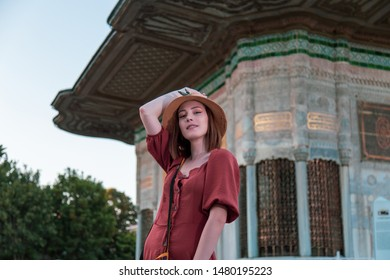 Beautiful girl with orange colored dress posing with Ahmet III Fountain during sunset from Istanbul