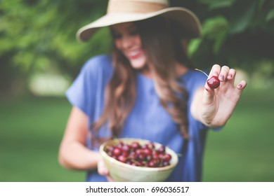 Beautiful girl out picking fresh cherries from tree