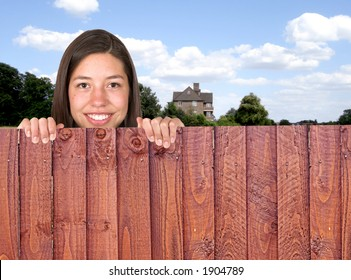 beautiful girl over a fence with a house in the background