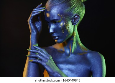 Beautiful girl in paint. Art portrait in Blue and green Light. make-up. Fairy beauty young woman in color Paint