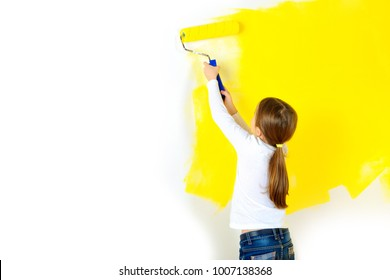 beautiful girl paints a roller against a wall in a room, repairs in the house