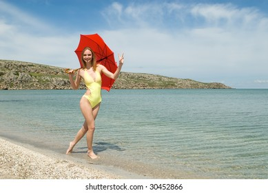 The beautiful girl with a parasol on seacoast