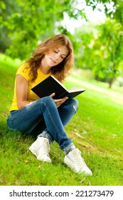 Beautiful girl in the park holding a book and day dreaming.