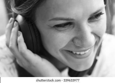 Beautiful girl in a park listening to the sound of music in the headphones (soft focus)