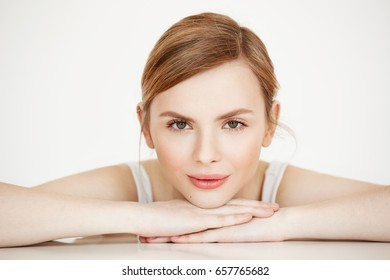 Beautiful girl with perfect clean skin smiling looking at camera sitting at table over white background. Beauty spa and cosmetology.