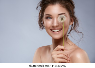 beautiful girl with perfect smile closing one eye with dandelion flower on grey background, copy space with attractive woman