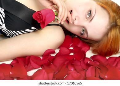 Beautiful girl in petals with rose