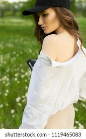 Beautiful girl photographer wearing a white shirt, beige trousers poses outdoors with a vintage camera against a background of meadow full of wild flowers. Lifestyle and commercial design. Copy space.