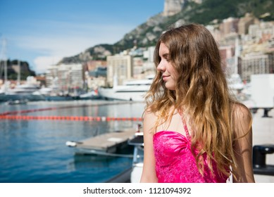 A beautiful girl in a pink dress stands on the background of Monaco