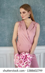 Beautiful girl in a pink jumpsuit holding flowers in studio at the window