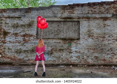Beautiful girl in pink red dress with red helium balloons in hand inside of abandoned place with big ruined brick graffiti wall on background staying back to viewers. HDR image