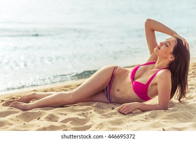 Beautiful girl in pink swimsuit is lying with closed eyes, enjoying and smiling while sunbathing on the beach