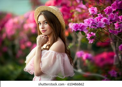 Beautiful  girl in pink  vintage dress and straw hat standing near colorful flowers. Art work of romantic woman .Pretty tenderness model looking at camera.