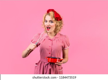 Beautiful girl in pin-up style with whisk. Cooking concept. Retro style housewife whisking mixture for baking. Excited pin up woman cooking in kitchen. Cooking, baking, confectioner, cuisine concept.