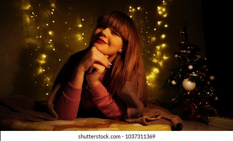 Beautiful girl in plaid blowing kiss. Female person with red lips and cute bangs enjoying holiday. Pretty woman smiling on camera.