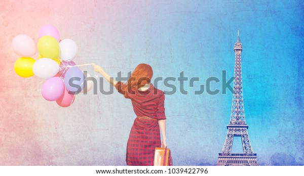 Beautiful girl in plaid dress with multicolored balloons on Eiffel tower background