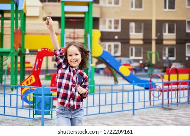 a beautiful girl in a plaid shirt on the Playground is laughing . One hand up