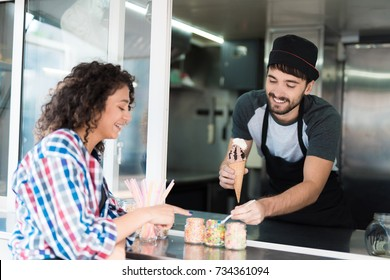 A beautiful girl in a plaid shirt ordered chocolate ice cream. A man in a mobile diner gives her ice cream. They both smile at each other. The man adds to the creamy whipped cream