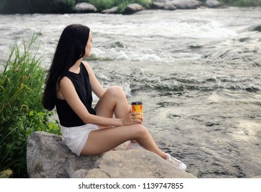 Beautiful girl with plastic cup sits on the river bank