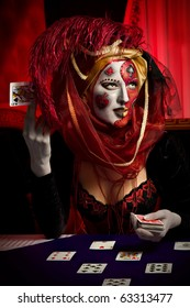 Beautiful girl with playing cards and cool Venetian mask makeup over vintage interior