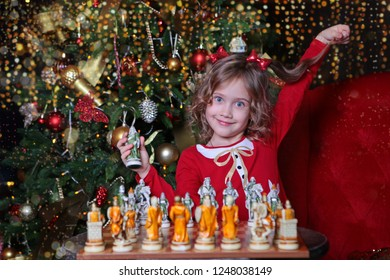 Beautiful girl playing chess near the Christmas tree. The concept of New year or Christmas. Emotional childhood.