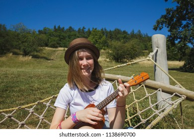 Beautiful girl playing ukulele - hawaiian guitar in hammock