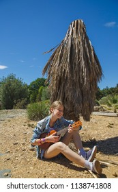 Beautiful girl playing ukulele - hawaiian guitar on a summer day