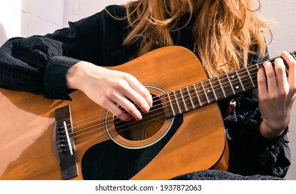 Beautiful girl plays the acoustic guitar. Guitarist on a white background.