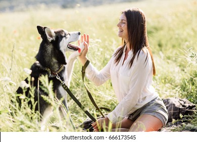 Beautiful girl plays with a dog (black and white husky with blue eyes) green field.