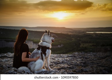 Beautiful girl plays with a dog, grey and white husky, in the mountains at sunset. Indian girl and her wolf