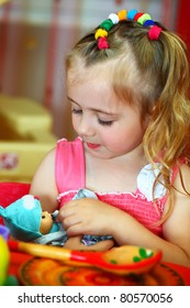 Beautiful girl plays with a doll