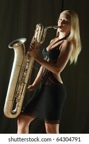 The beautiful girl plays a saxophone