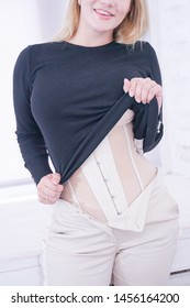 beautiful girl with plus size figure shows hidden under normal clothes training corset