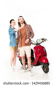 beautiful girl pointing with hand and young man looking away, standing near red scooter isolated on white
