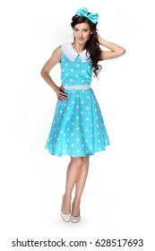 Beautiful girl in a polka-dot dress with a blue bow on a white background