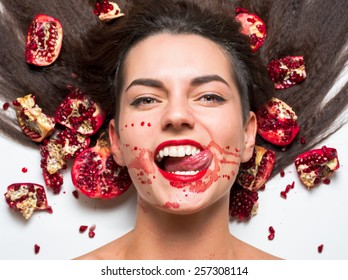 A beautiful girl in pomegranate juice. lying on a white background