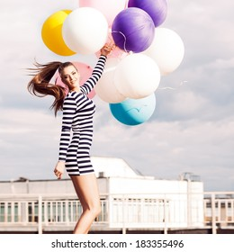 beautiful girl with ponytail hair in short black and white striped dress and white high sneakers jumps holding bunch of multicolored balloons